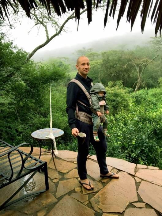 Man staat op een terras voor de jungle met zijn baby voor zich in een harnas, op zijn borst