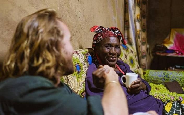 Charlie op bezoek bij Mama Rose die een tas thee vastheeft terwijl ze elkaar een hand geven in de homestay bij de Taita Hills