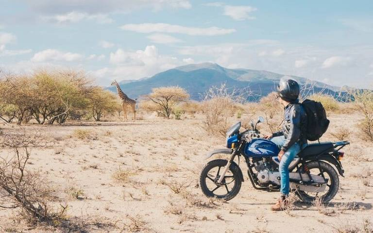 Man op motor met giraffe op de achtergrond