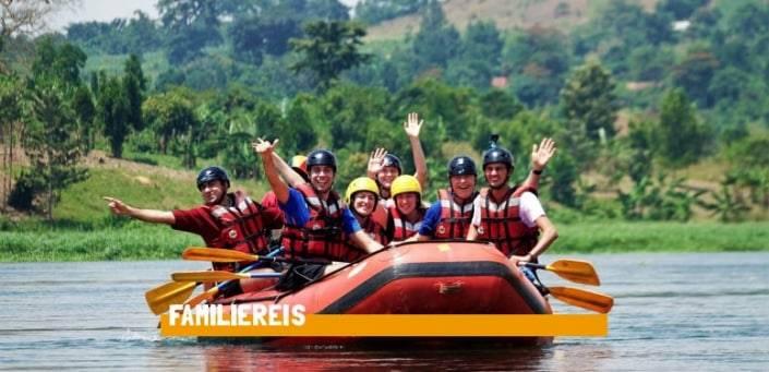 Familie zit in een rubberboot met reddingsvesten en zwarte helmen op terwijl ze allemaal lachen en zwaaien naar de camera