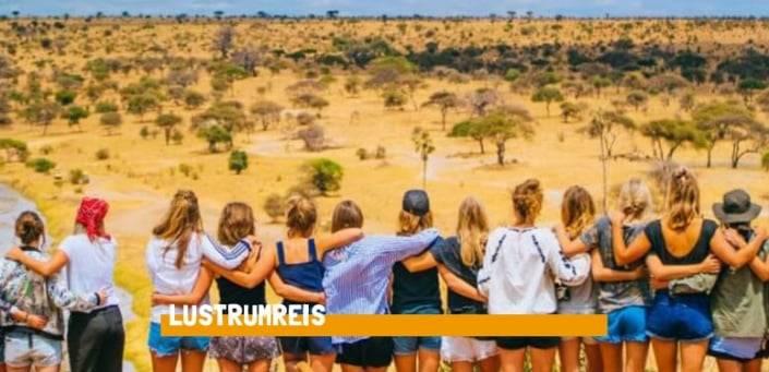 Aantal vrouwen die elkaar vasthouden met de ruggen naar de camera, kijkend naar het uitzicht over de savanne