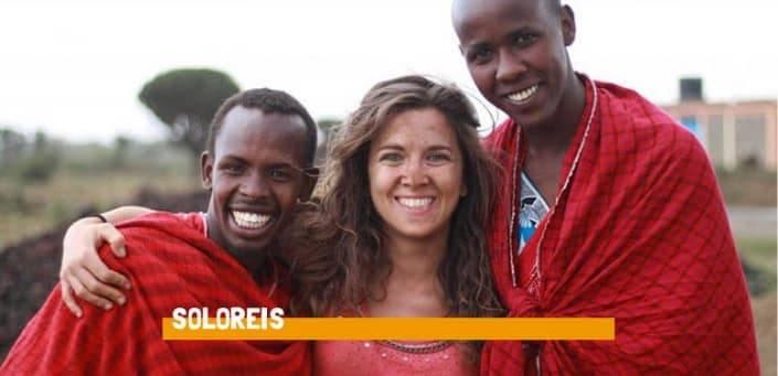 Vrouw staat tussen twee mannen met rode dekens om zich heen en ze lachen allen naar de camera