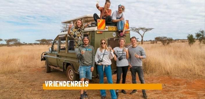 Groep vrienden staan voor en zitten op een groene jeep in de savanne