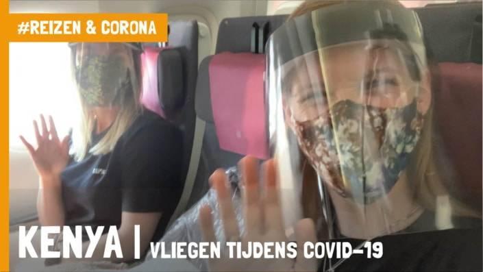 Twee vrouwen in het vliegtuig met een face shield en mondmasker die naar de camera zwaaien