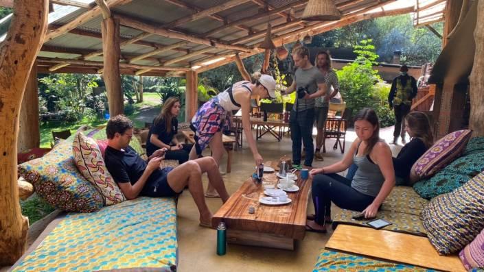Groep mensen samen onder een houten afdak met een tafeltje vol kopjes en bordjes