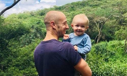 Vader houdt zijn kindje vast en lacht met bomen en groen op de achtergrond