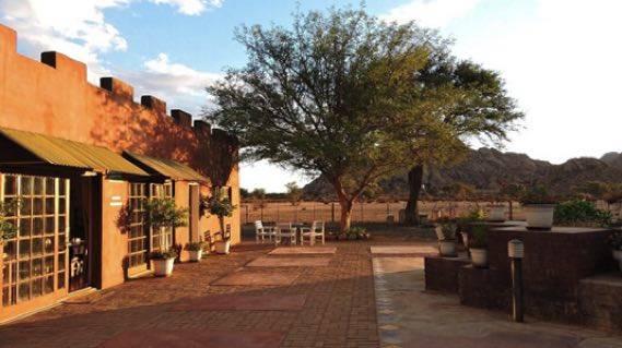 Zijaanzicht van de Savanna Guest Farm met een boom erlangs