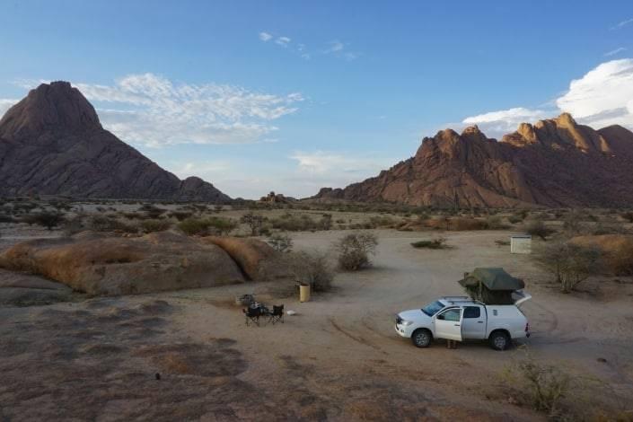 Jeep staat in de woestijn in Namibië met daktent, tussen de rotsen