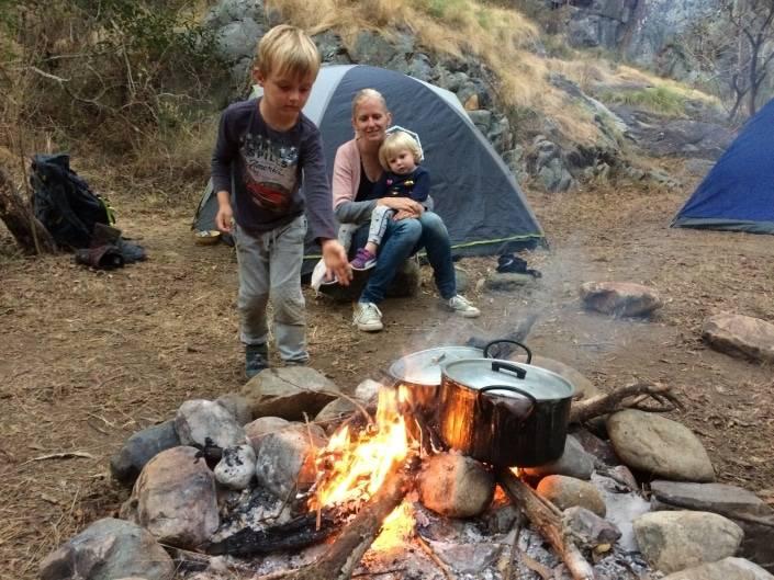 Mama zit voor haar tent met baby'tje op de schoot en een ander kindje staat bij het vuur met potten