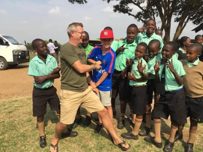 Vader en zoon bij een groep afrikaanse kinderen