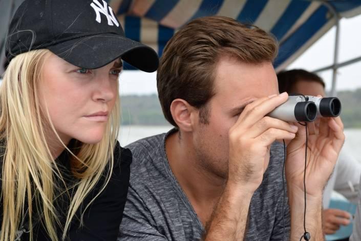 Man kijkt door een verrekijker met een vrouw langs hem