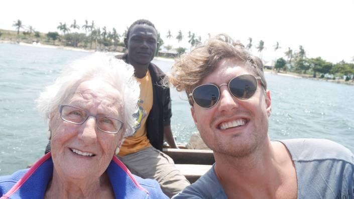 Man met zonnebril samen met zijn oma in een bootje met de bestuurder achter hen