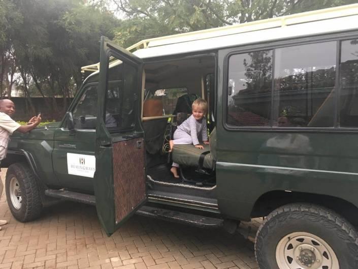 Peuter klimt op de zetel in een groene safari-jeep