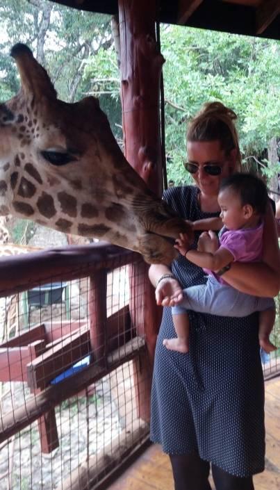 Mama met kindje in haar armen terwijl ze de mond van een giraf aaien