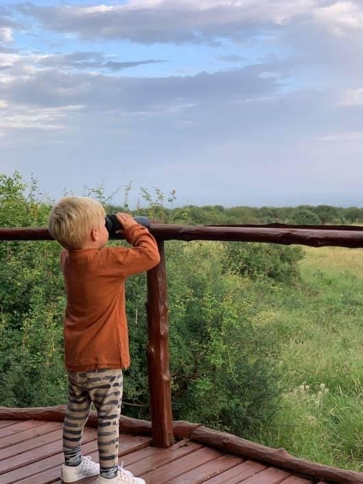 Klein kindje zit gehurkt op een houten terras en kijkt met een verrekijker het groen in
