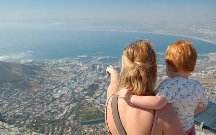 Mama houdt haar baby vast en wijst voor zich uit, naar de stad en zee onder hen