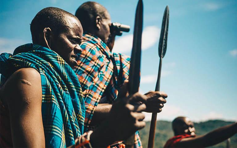 Maasai man wijst in de verte met bossen op de achtergrond